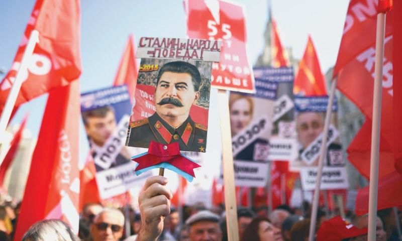 MOSCOW: Russian Communist party supporters carry red flags and the portrait of former Soviet leader Josef Stalin during a rally against the government's proposed reform hiking the pension age.—AFP