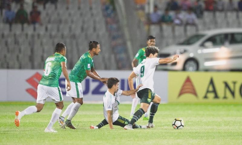 DHAKA: Pakistan's Mohammad Ali (R) and Mahmood Khan vie for the ball with Bangladesh players during their SAFF Cup Group 'A' match at the Bangabandhu National Stadium on Thursday.—Courtesy SAFF