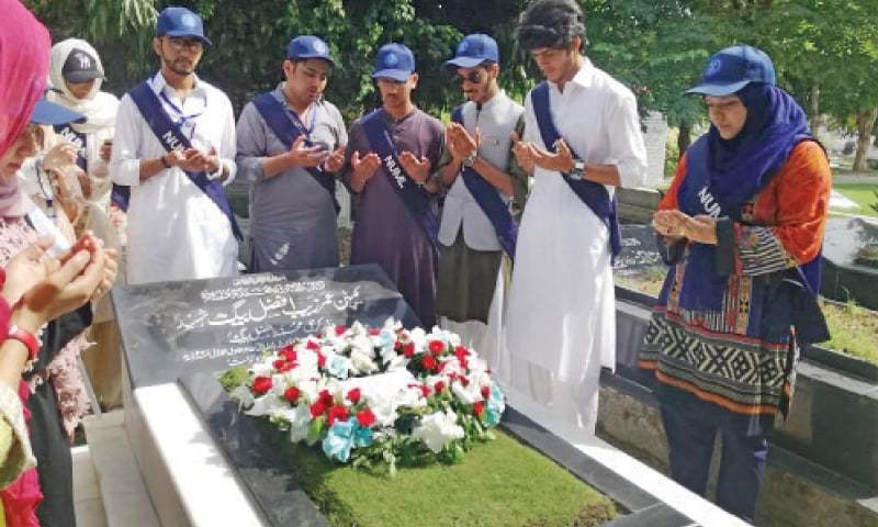 Faculty members and students of Numl offer fateha at the grave of martyred Captain Umerzeb Afzal Beg. — Dawn