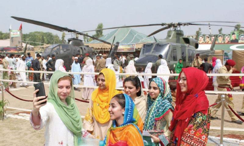 Visitors take selfies at a Defence Day exhibition in Peshawar. — INP