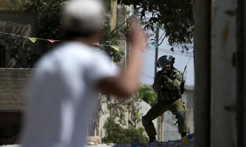 An Israeli soldier aims at a Palestinian protester following a weekly demonstration against the expropriation of Palestinian lands by Israel. —AFP