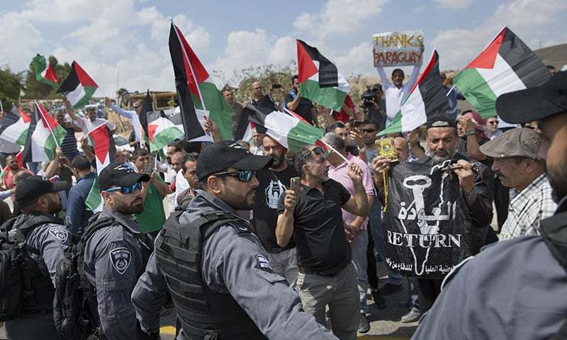 Israeli border police surround protesters flying Palestinian flags and chanting anti Israel slogans. —AP