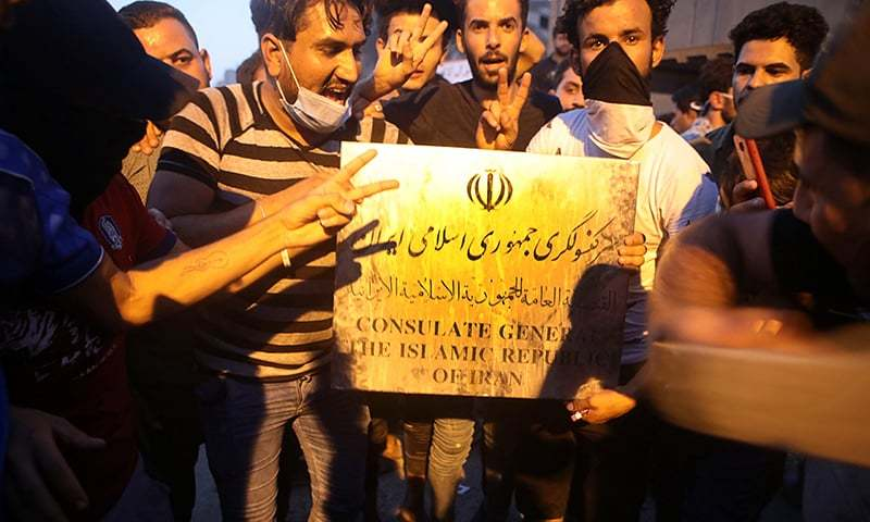 Protesters hold a sign belonging to the Iranian consulate building before storming and burning it in Basra. —AP