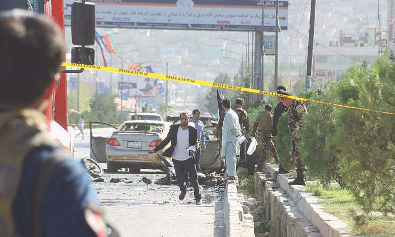 KABUL: Security personnel inspect the site of the suicide attack on Sunday.—AFP