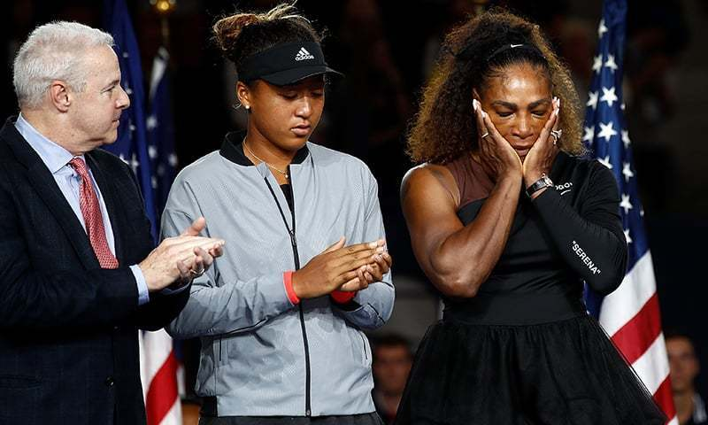 Osaka stands alongside an upset Serena at the end of their US Open clash. — AFP