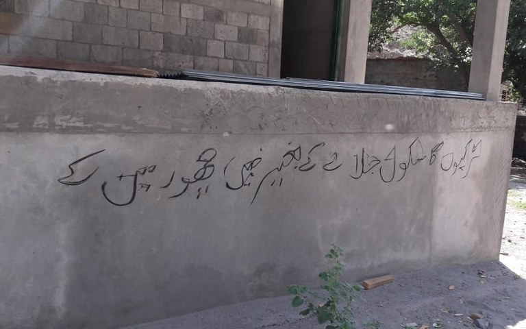 An inscribed threat on the wall of one of the torched schools reflects the arsonists' extremist mindset — Photo by author