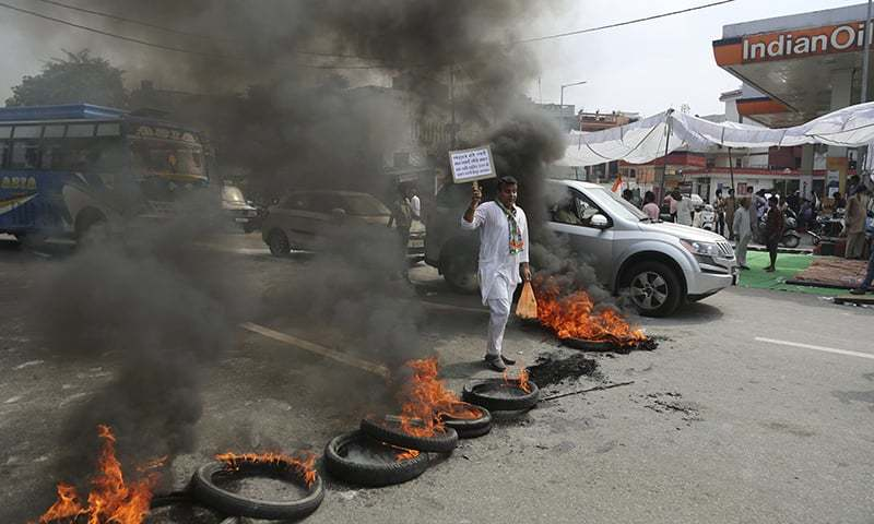Tires are set on fire by opposition Congress party activists to block traffic as one of them holds a placard during a protest against fuel price hike and other economy issues, in Jammu, India. — AP