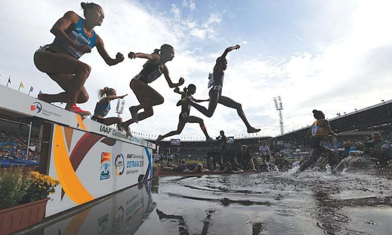 OSTRAVA: Athletes are silhouetted during the women's 3,000 metres steeplechase at the IAAF Continental Cup.—AP