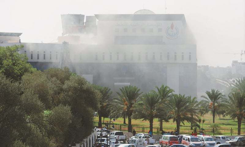 Tripoli: Smoke rises from the headquarters of Libya's state oil firm after three masked persons attacked it on Monday.—Reuters