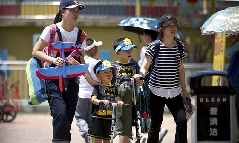 In this June 1, 2018, photo, women walk with children wearing matching outfits at a public park on International Children's Day in Beijing. — AP