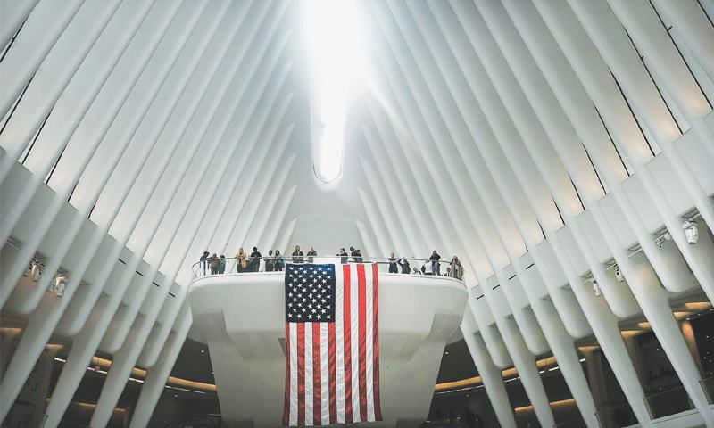 NEW YORK: People at the World Trade Centre Oculus wait as the retractable skylight is opened on Tuesday during a commemoration ceremony for the victims of the terrorist attacks of Sept 11, 2001. The skylight, which gives a view of One World Trade, is only opened on September 11.—AFP