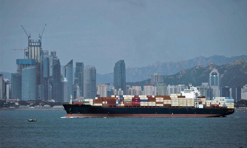 A container ship sails by the business district in Qingdao in east China's Shandong province on Thursday.—AP