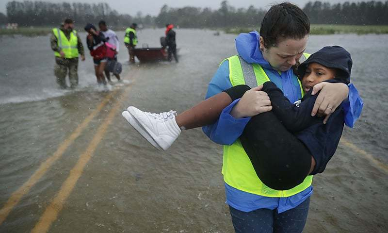 Volunteers from the Civilian Crisis Response Team help rescue three children from their flooded home in James City, United States. —AFP