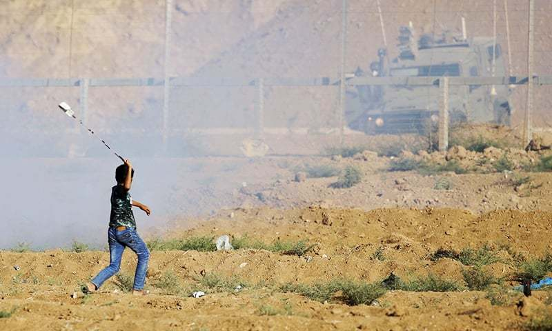 A Palestinian boy uses a slingshot to throw a stone toward Israeli forces firing tear gas during a demonstration along the Israeli fence East of Gaza City on September 14, 2018. —AFP