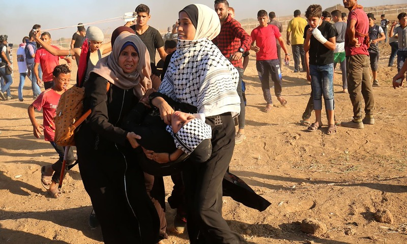 Palestinians carry an injured protester. —AFP