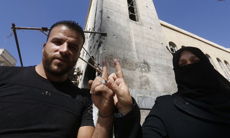 A man and a woman show their ink-stained index fingers after voting for Syria's first local elections since 2011. —AFP