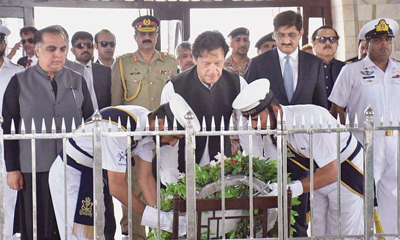 KARACHI: Prime Minister Imran Khan laying a floral wreath at the Quaid-i-Azam's mausoleum on Sunday. Sindh Governor Imran Ismail and Chief Minister Syed Murad Ali Shah are also seen.—Online