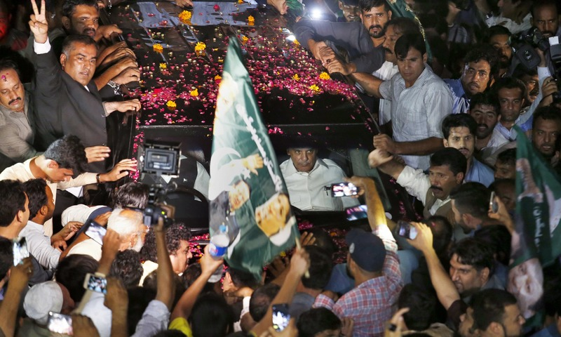 Vehicle carrying Nawaz Sharif is surrounded by his supporters following his release from prison in Rawalpindi. —AP