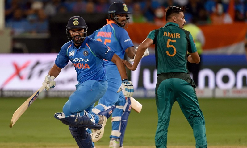 Rohit Sharma and Shikhar Dhawan run between the wickets as  Mohammad Amir looks on. — AFP