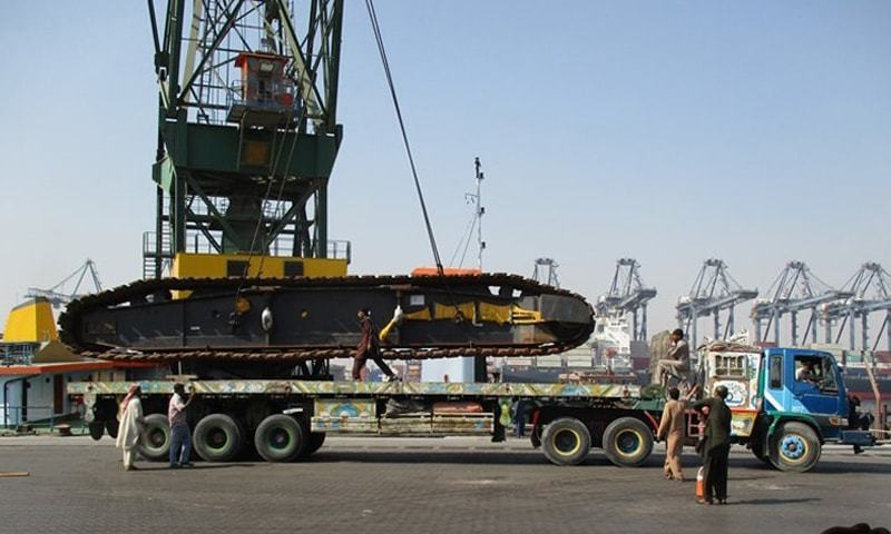 Imported earth-moving machinery is being loaded on a truck at the Karachi port. After surging in the last three years, the machinery imports have now started reversing the trend with second consecutive drop in the first two months of this fiscal year.—File photo