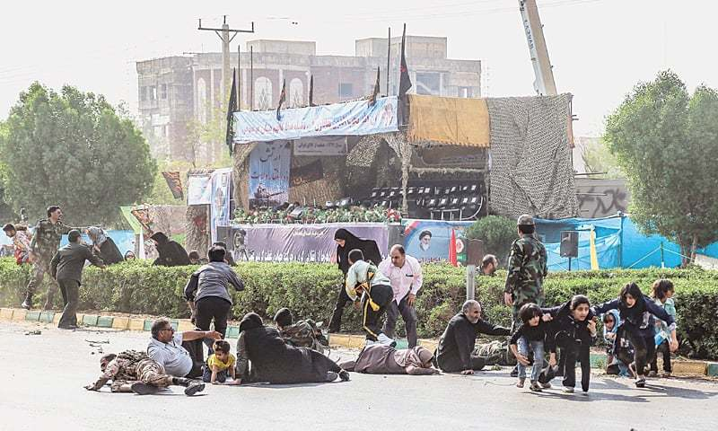 AHVAZ (Iran): Iranian men, women and children seek cover at the scene of a gun attack on a military parade that was marking the anniversary of the outbreak of the 1980-1988 war with Saddam Hussein's Iraq on Saturday. Dozens of people were killed with many others wounded in the rare assault.—AFP