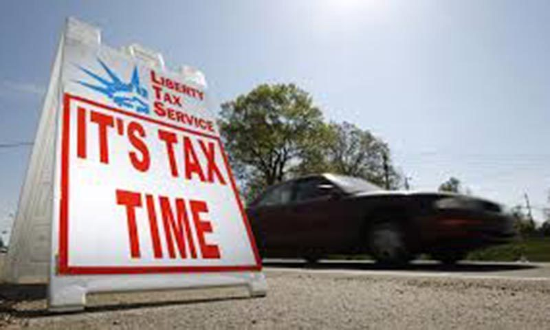 File photo of a car passing a sign advertising tax return services in Falls Church, Virginia April 8, 2010.— Reuters/File