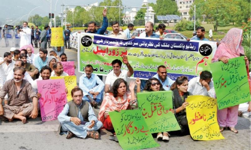 In this photo taken on Monday, Radio Pakistan employees hold up placards at the protest on Constitution Avenue in Islamabad. — White Star