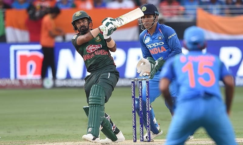 Bangladesh batsman Liton Das plays a shot as Indian wicketkeeper Mahendra Singh Dhoni (R) looks on. — AFP