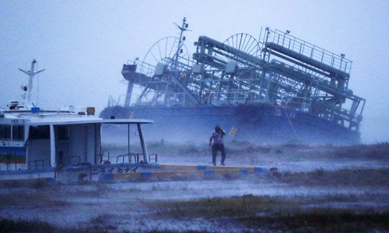 A vessel's rear tilts on one side as it ran ashore at a pier with a typhoon approaching Yonabaru, Okinawa prefecture. —AP