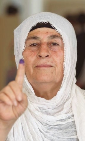 An Iraqi Kurdish woman shows her ink-stained finger after casting her ballot. — AFP