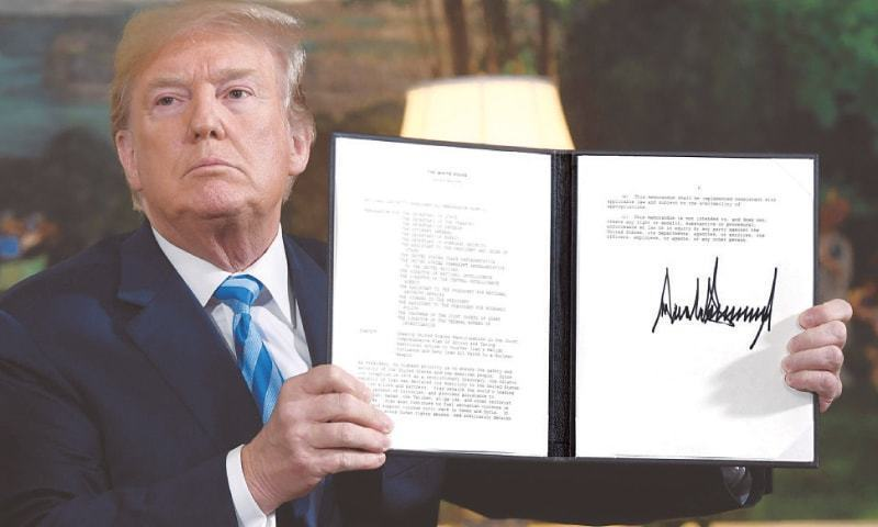 President Trump shows a document which he signed in May to pull US out of the Iran deal which put curbs on Tehran's nuclear programme in return for lifting of sanctions. — File  AFP
