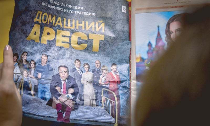 a woman holding a magazine with a promotional ad for Russian comedy series House Arrest.—AFP