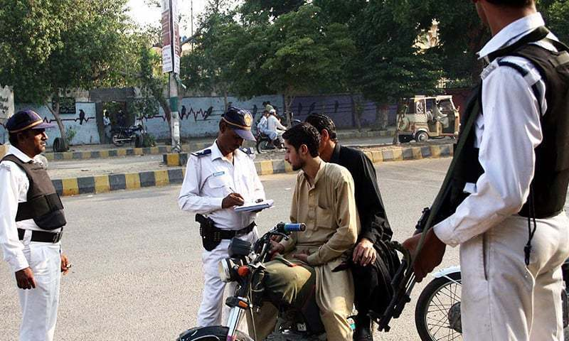 In this file photo, traffic police officials communicate with motorcyclists.