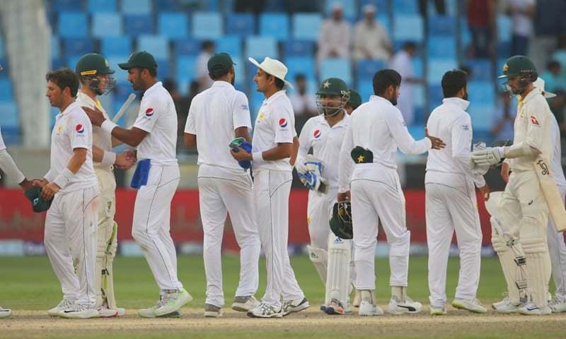 دبئی ٹیسٹ ڈرا پر ختم ہونے کے بعد پاکستان اور آسٹریلیا کے کھلاڑی ایک دوسرے سے مصافحہ کر رہے ہیں— فوٹو: اے ایف پی