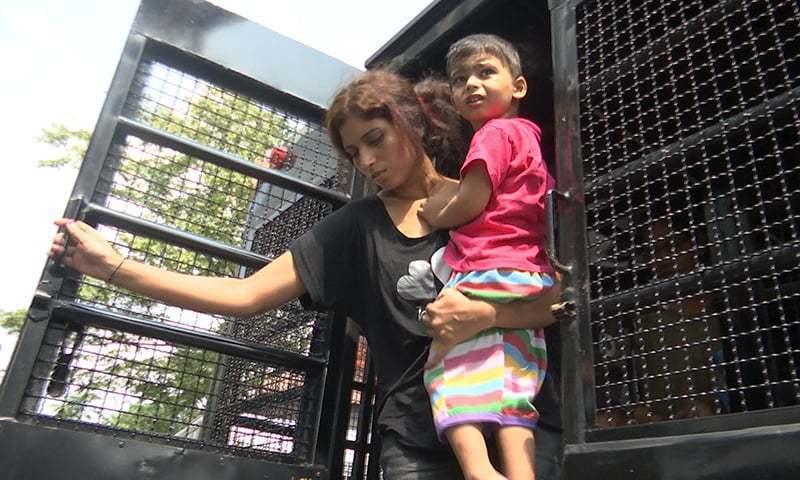 پاکستانی پناہ گزیں خاتون بنکاک کے امیگریشن حراستی مرکز آمد پر پولیس کے ٹرک سے اتر رہی ہے— فوٹو: اے پی