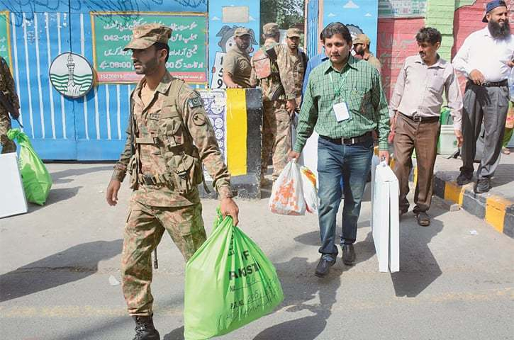 Members of polling staff and security personnel bring material for the by-elections to a polling station set up at a government school.—Online