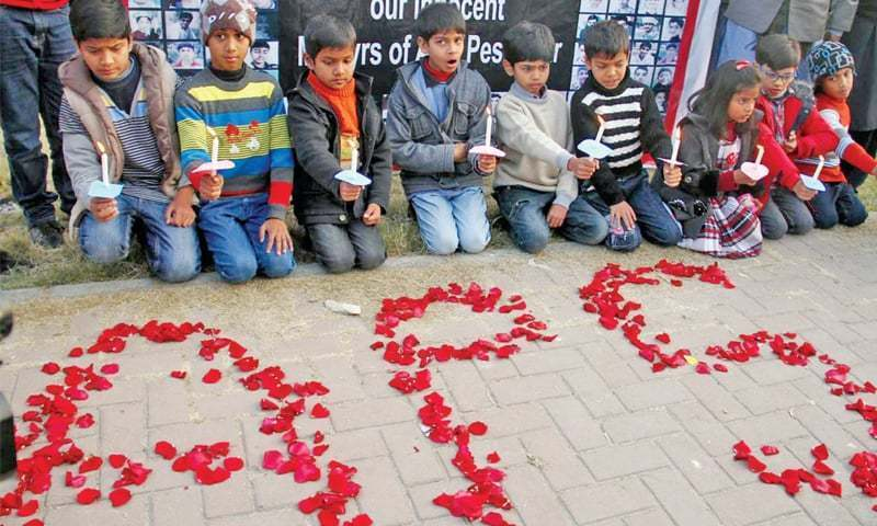 This file photo shows children from Sweet Homes pay tribute to APS attack victims.