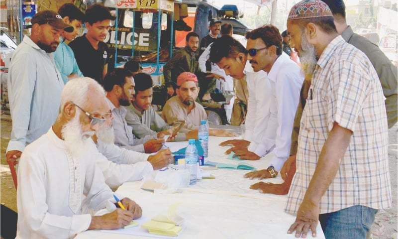 Voters seek information about their polling booths at a camp set up by a political party in NA-243 on Sunday. —Faysal Mujeeb/ White Star