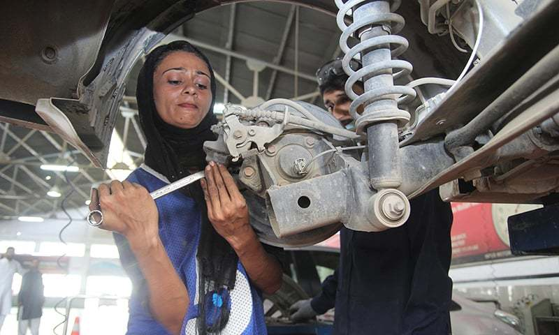 In this picture taken on September 1, 2018, motor mechanic Uzma Nawaz fixes a car at an auto workshop in Multan. — AFP