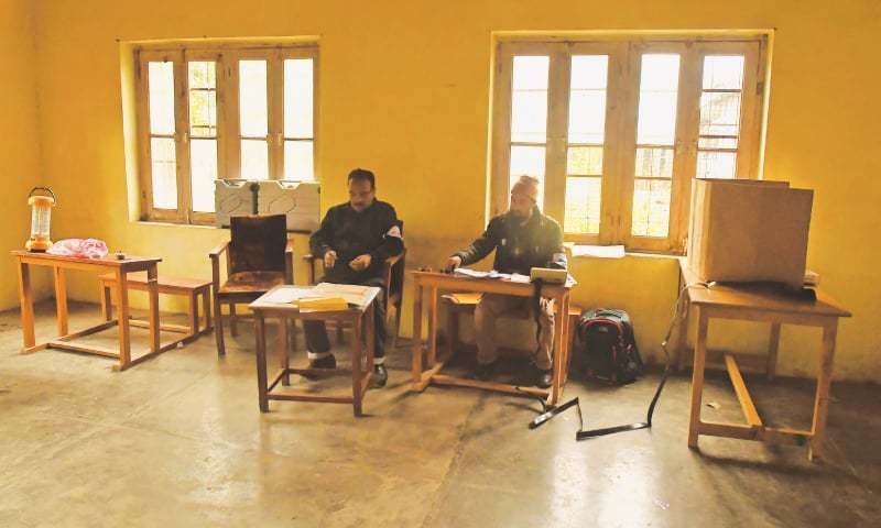 Election staff wait for voters at an almost empty polling station in Srinagar. — AFP