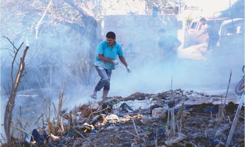 In this file photo a man uses dirt to put out a fire at the scene of a reported air strike in the district of Jisr al-Shughur in the Idlib province in  September. — AFP