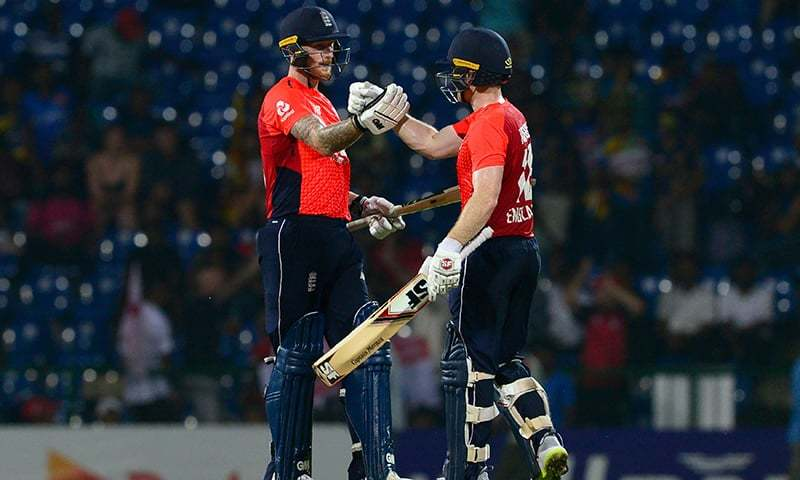 England cricket captain Eoin Morgan (R) teammate Ben Stokes (L) celebrates after victory in the third one day international (ODI) cricket match between Sri Lanka and England at the Pallekele International Cricket stadium in Pallekele on October 17, 2018. — AFP