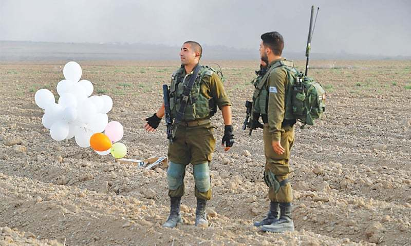 Israeli soldiers checking an incendiary device launched by Palestinian protesters from the Gaza Strip. — AFP