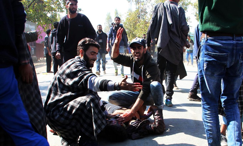 Kashmiri men gesture as another lies on the ground after a blast near a residential house where three suspected militants were killed during a gunfight with Indian forces in Kulgam. —AFP