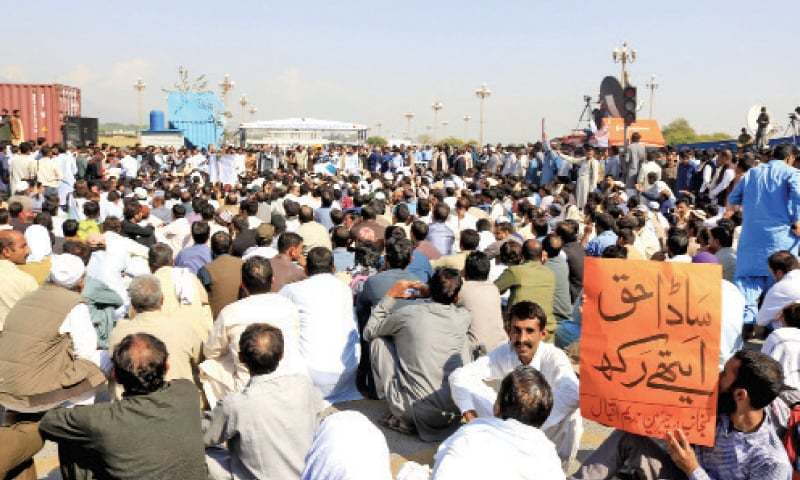 USC employees stage a sit-in at D-Chowk in Islamabad on Monday. — Photo by Mohammad Asim