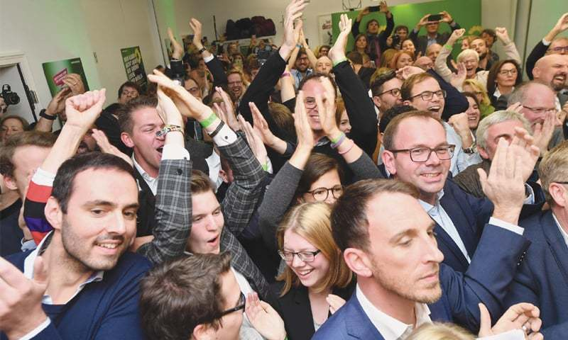 Wiesbaden (Germany): Supporters of the Green party welcome the first exit polls during the state elections.—AFP