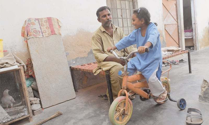 Rickshaw driver Mohammad Rasheed talks to his daughter Nabeeha in their home in Karachi.—AFP
