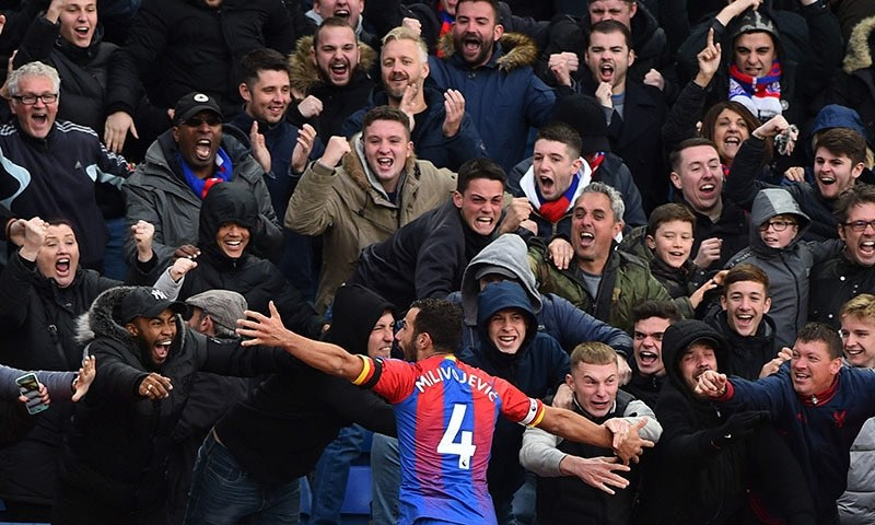 Crystal Palace's Serbian midfielder Luka Milivojevic celebrates with the crowd after scoring his and his team's second goal to equalise 2-2 during the English Premier League football match between Crystal Palace and Arsenal at Selhurst Park in south London on October 28, 2018. — AFP