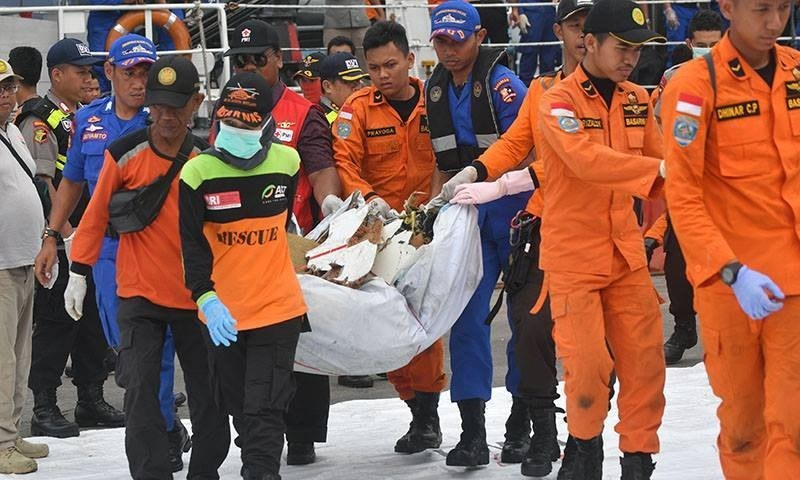 Indonesian search and rescue personnel carry recovered debris from the ill-fated Lion Air flight JT 610 at a port in northern Jakarta on Tuesday. — AFP