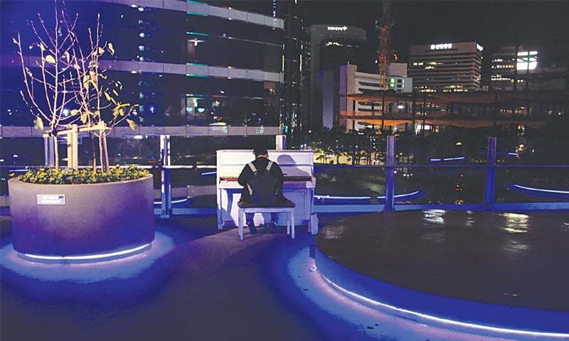 Sitting on Seoullo 7017, a man plays the piano, enjoying the silent tranquillity of the night.—Photo by writer